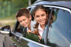 Portrait of children looking outside the car window. Cheerful kids looking by car window royalty free stock photos