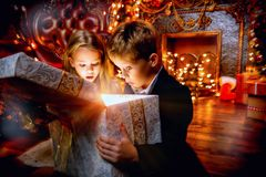Surprised with gifts. A portrait of children opening a gift box. Merry Christmas, happy New Year. Luxurious apartment with christmas lights and decorations royalty free stock photos