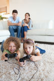 Portrait of children playing video games while their parents are. Watching in their living room stock photos