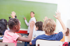 Portrait of children raised their hands in a multi ethnic classr Stock Image