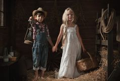 Portrait of children in a rustic barn Royalty Free Stock Image