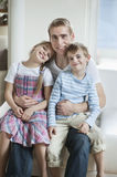 Portrait of children sitting on father's laps Stock Photo
