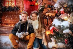 Siblings on the porch. A portrait of children sitting on the porch of their house together. Merry Christmas, happy New Year. Yard with a christmas tree, lights royalty free stock images