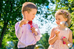Portrait of children with soap bubbles. Outdoors in the park stock photography