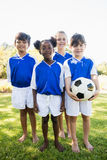 Portrait of children soccer team standing bare feet. In park Stock Images