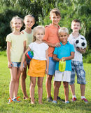 Portrait of children standing with toys on green meadow in park Stock Image