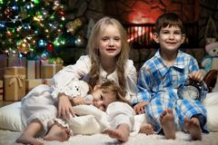 Portrait of children under the Christmas tree by the fireplace. Three young children under the Christmas tree by the fireplace Royalty Free Stock Images