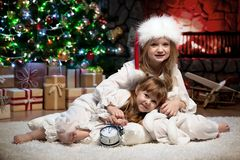 Portrait of children under the Christmas tree by the fireplace. Two girls under the Christmas tree by the fireplace Royalty Free Stock Image