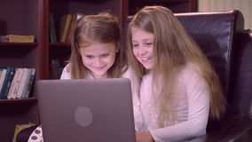 Portrait children use computer indoors. Two Caucasian sisters have fun watching some video or cartoon using laptop indoors. Two small girls with long blond hair stock video footage
