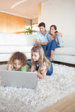 Portrait of children using a notebook while their parents are wa. Tching in their living room Stock Images