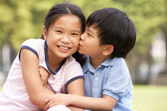 Portrait Of Chinese Boy And Girl Sitting In Park Royalty Free Stock Image