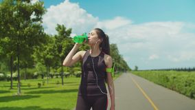 Thitsty woman having energy drink during workout. Portrait of chinese female athlete drinking energy drink while running across city park on sunny morning stock video footage