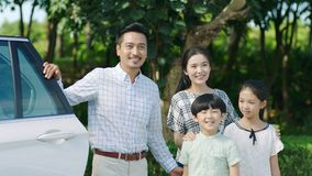 Asian family standing beside car looking forward and smiling stock photography