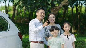 Asian family standing beside car smiling while father pointing stock images