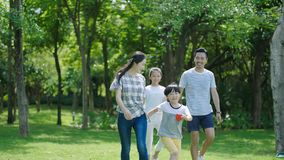 Chinese family smiling & walking together in park stock photo
