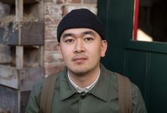 Portrait of chinese young man in front of the door.  Royalty Free Stock Photos