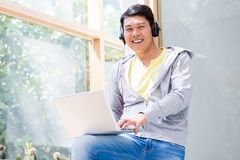 Chinese young man wearing casual clothes while using a laptop. Portrait of Chinese young man wearing casual clothes while using a laptop in a modern office or at Royalty Free Stock Images