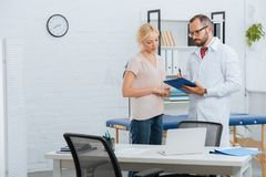 portrait of chiropractic in white coat with notepad and female patient having conversation