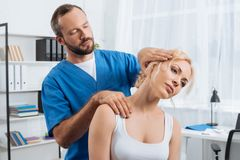 portrait of chiropractor stretching neck of woman