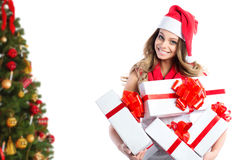 Portrait of a Christmas woman with gifts in santa hat near the Christmas tree. Stock Photo