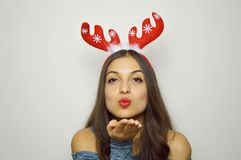 Portrait of christmas woman with red lips blowing sends air kiss with reindeer horns on her head. Over gray background Royalty Free Stock Photo