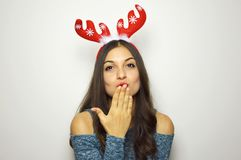 Portrait of christmas woman with red lips blowing sends air kiss with reindeer horns on her head. Over gray background Royalty Free Stock Photography