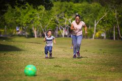 Happy Asian Indonesian mother playing football with little 5 years old son running together excited laughing having fun in soccer stock image