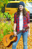 Portrait of classic guitar girl player standing at yellow van and autumn yellow tree background Royalty Free Stock Photo