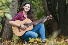 Portrait of classic guitar player student girl leaning tree trunk at autumn forest background Royalty Free Stock Image