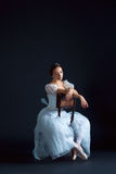 Portrait of the classical ballerina in white dress on black background Stock Images