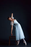 Portrait of the classical ballerina in white dress on black background Stock Photo