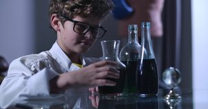 Portrait of clever Caucasian boy in eyeglasses looking at flasks with liquids and gesturing yes. Young teenager