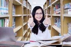 Clever high school student showing thumbs up. Portrait of clever high school student girl studying in the library while showing thumbs up Stock Image