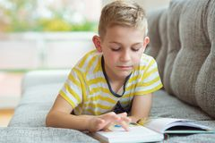 Portrait of clever little boy with reading book Royalty Free Stock Photography