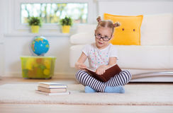 Portrait of clever little girl sitting with book on the floor Stock Photography