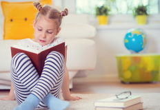 Portrait of clever little girl sitting with book on the floor Stock Images