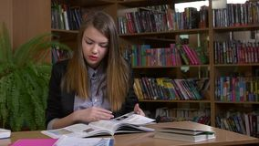Portrait of clever student with open book reading. It in college library, red lips, the book, looking for material, slow motion stock video footage