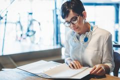 Portrait of clever student reading book in college library Stock Photography