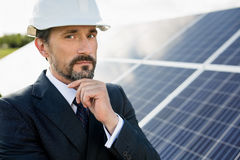 Portrait of client in white helmet at solar power station. Man in business suit holding hand to his chin Royalty Free Stock Photo