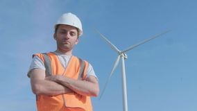 PORTRAIT: Close shot of adult engineer in orange vest and white hard hat with wind turbines on background looking at. Camera stock video footage