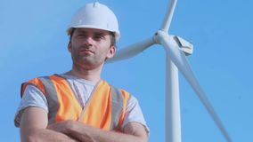 PORTRAIT: Close shot of adult engineer in orange vest and white hard hat with wind turbines on background looking at. Camera stock video