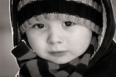 Portrait close up of boy in black and white. Black and white portrait of a cute adorable young boy who is wearing a scarf and a dark coloured hooded top. The royalty free stock images