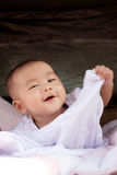 Portrait close up face of asian baby lying on bed and playing wi Stock Image