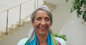 Mature woman at home. Portrait close up of a mature mixed race woman laughing to camera in the hallway of her home stock video footage