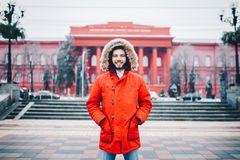 Free Portrait, Close-up Of A Young Stylishly Dressed Man Smiling With A Beard Dressed In A Red Winter Jacket With A Hood And Fur On His Stock Photos - 132792433
