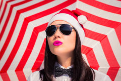 Portrait close up of a pretty young woman in Santa Claus hat. And sunglasses with bright painted lips next to striped background stock image