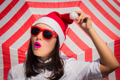 Portrait close up of a pretty young woman in Santa Claus hat. And sunglasses next to striped background royalty free stock images