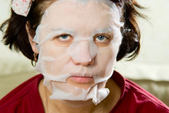 Portrait  close-up woman applying rejuvenating facial mask on h Royalty Free Stock Photo