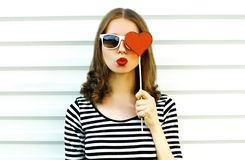 Portrait close-up woman blowing red lips sending sweet air kiss hiding her eye with red heart shaped lollipop on white wall. Background royalty free stock photo
