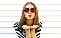 Portrait close-up woman blowing red lips sending sweet air kiss on white wall. Background stock photo
